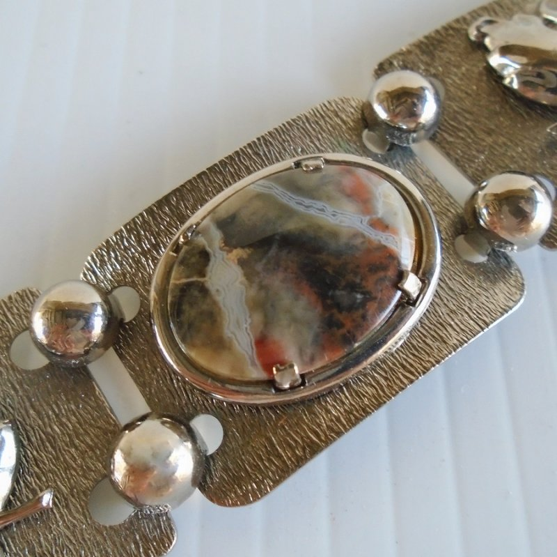 Large Agate stone centerpiece in this Silvertone link bracelet. Red, white, brown, gold, and gray coloring. 7.5 inches long.