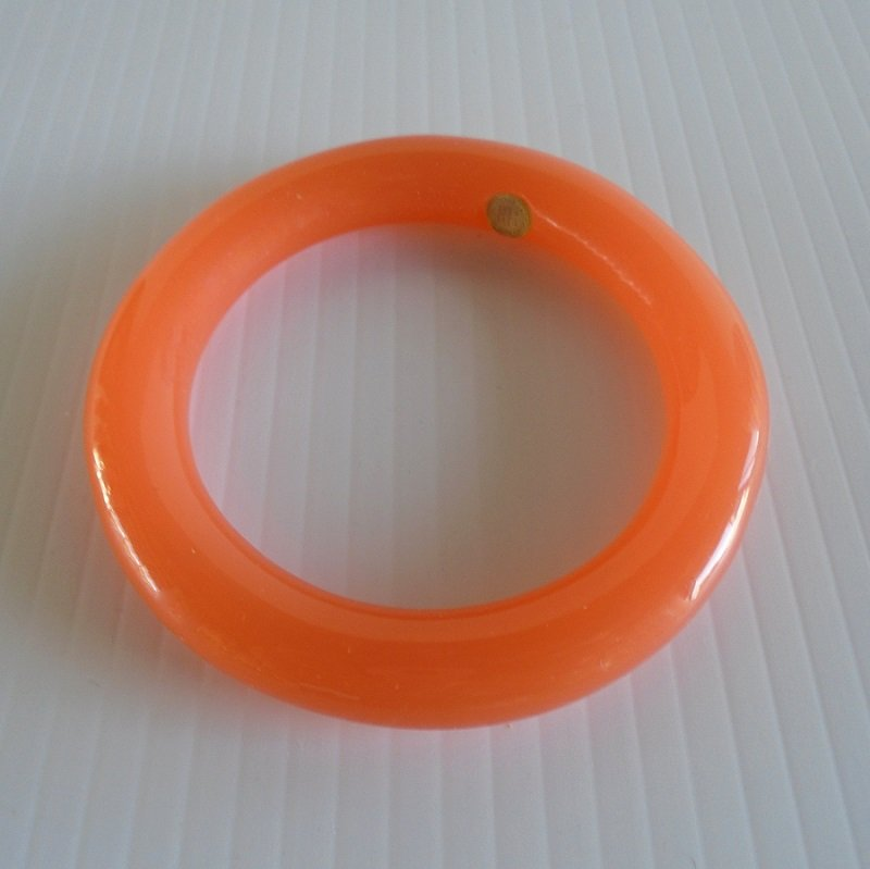 Givenchy bangle bracelet, orange in color. Made of Lucite. 2.5 inch opening. Has the Givenchy logo on the inside. Estate purchase.