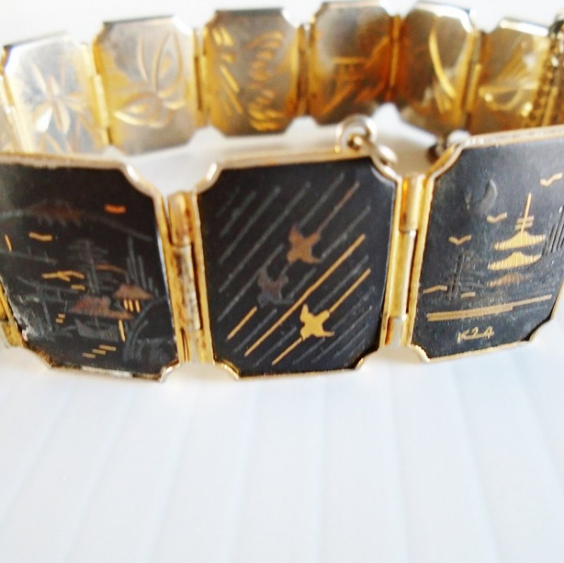 Damascene link bracelet. 11 panels. Features birds, flowers, and buildings. Black and gold in color. Safety chain and snap lock clasp. 1960s-70s.