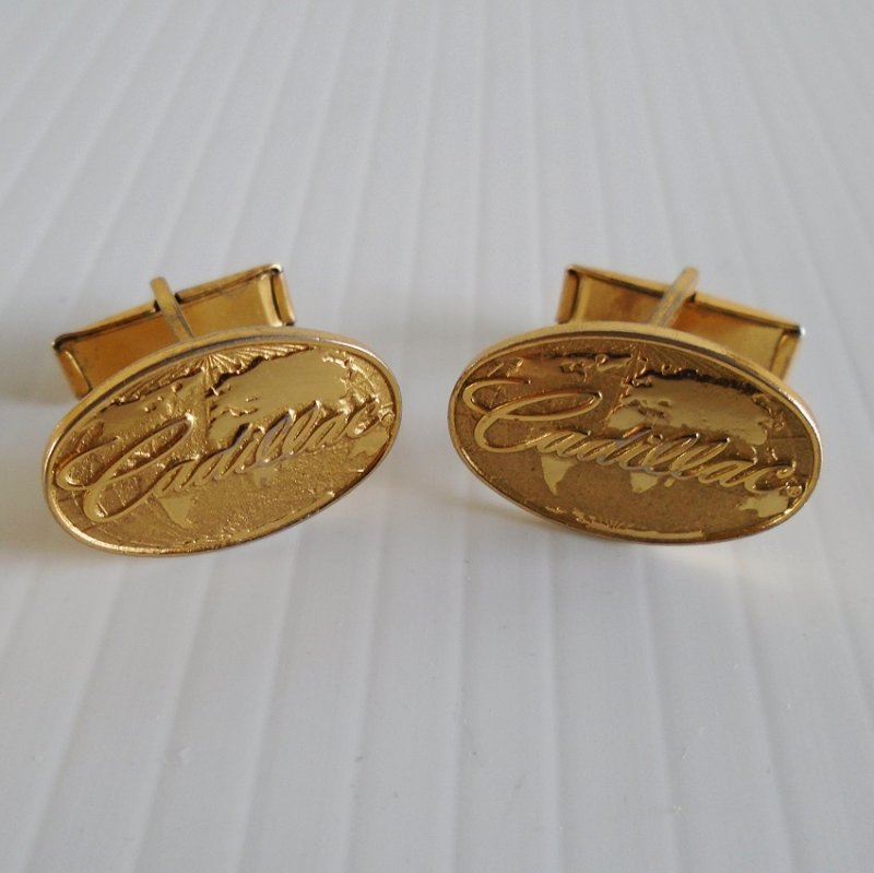 Goldtone Cadillac cufflinks. The word Cadillac is sitting on a background of a globe of the world. At least 30 years old. Estate find.
