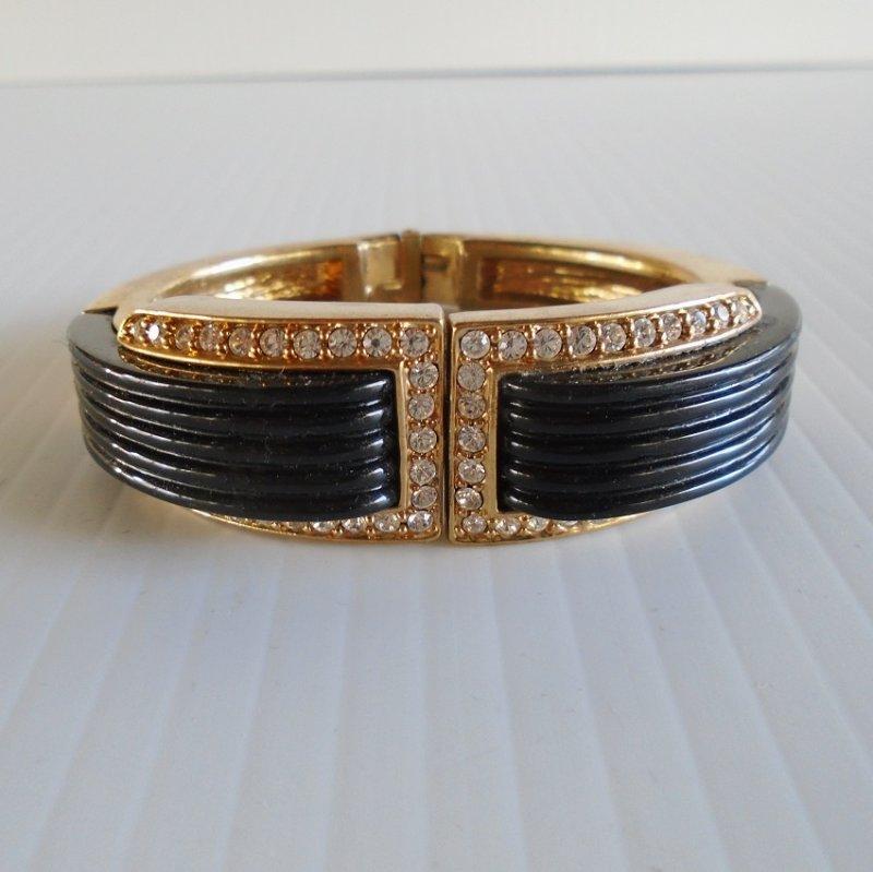Vintage estimated 1940s hinged clamper bracelet. Clear rhinestones, black bakelite, gold tone metal. Estate purchase.