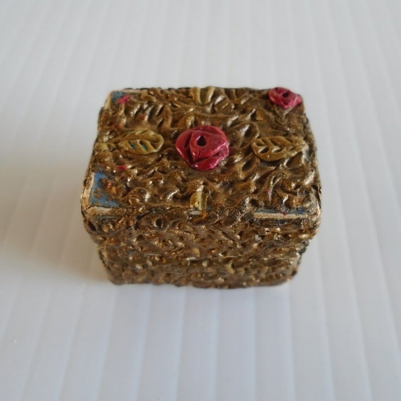 Gold color small pill box with pink roses, c1950s. Possibly made with paper mache. 1 by 1.25 inches, 1 inch tall.