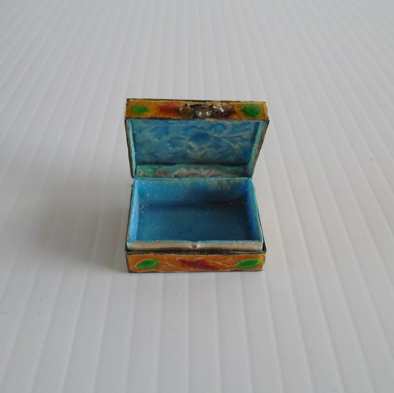 Gold color small pill box with flowers on lid and sides. Enameled.  Stated to be circa 1950s. 1.25 by 3/4 inches, 1/2 inch tall. Estate purchase.