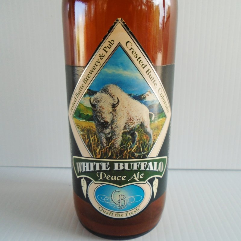 White Buffalo Peace Ale empty bottle. Size equivalent to a wine bottle. Crested Butte Colorado. Label is dated 1994. Vibrant colors on labels.