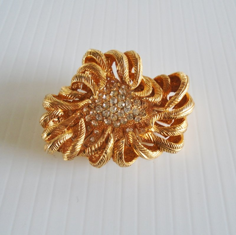 Floral brooch pin signed Castlecliff. Loaded with rhinestone. Gold in color. Dates between 1945 and 1977. Estate purchase.