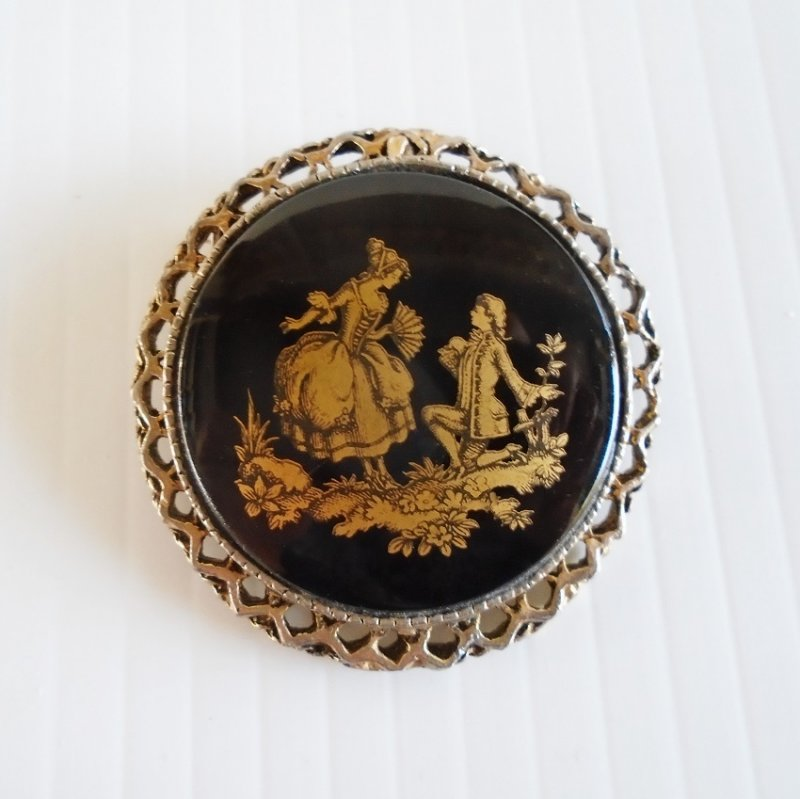 circa 1960s courting couple in colonial attire brooch. Goldtone on black enamel. Estate purchase.