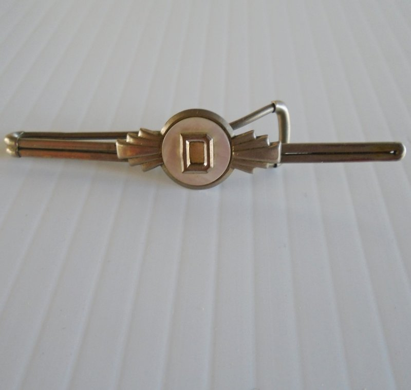 circa 1930s formal tie clip featuring the initial D on a Mother of Pearl background. Estate purchase.