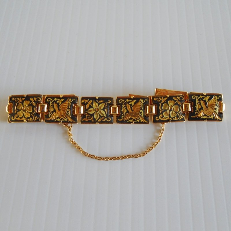 Damascene link bracelet. 10 panels. Features birds and flowers. Black and gold in color with possible 24k etching. Safety chain. 1960s-70s.