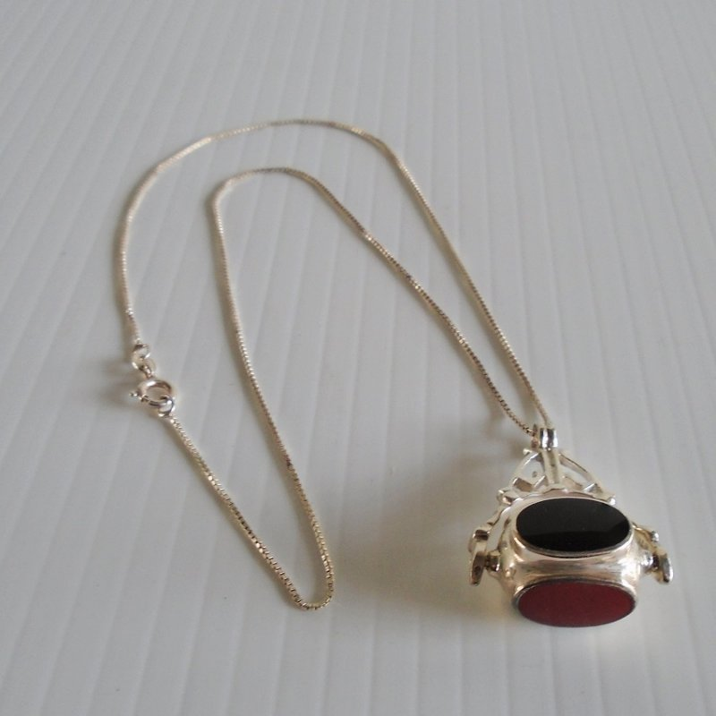 Spinning barrel necklace on 18 inch chain. Marked 925 and Italy. Each side has a different color stone of red, black, green, and ivory white. Estate purchase.