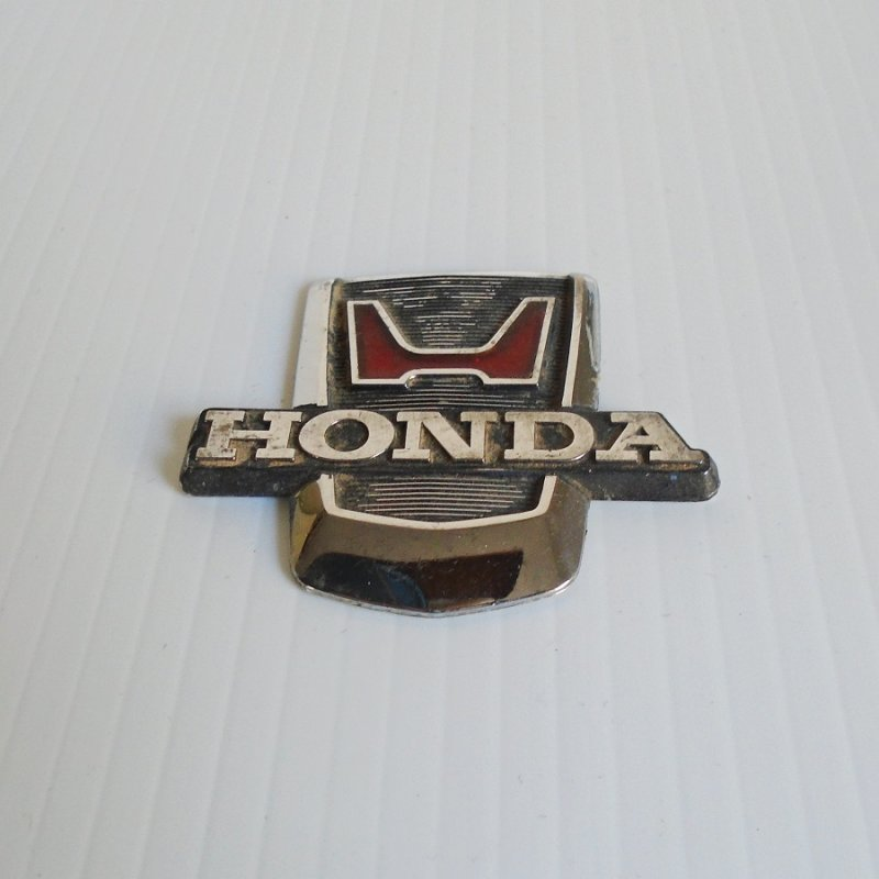 Honda vehicle emblem. Probably 1970s model. Possibly steering wheel centerpiece or grill decor. Approx 2 by 2.5 inches. Estate sale find.