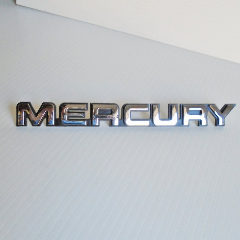 Front of Mercury vehicle nameplate emblem. Vintage, probably 1970s - 1980s model. 7.75 by 3/4 inches. Estate sale find.
