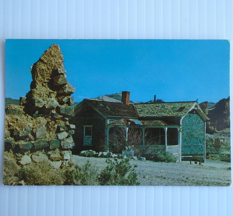 Vintage pre 1963 postcard of Rhyolite Nevada Bottle House. House was made with over 50,000 whiskey bottles in 1905. Postally unused.