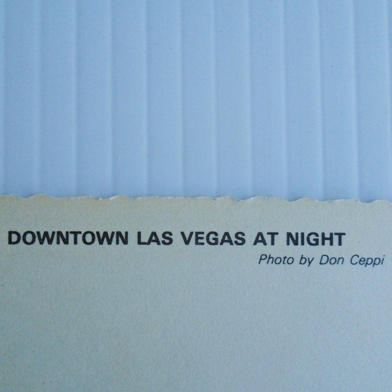 Vintage 1960s 1970s postcard of Downtown Las Vegas at dusk. Postally unused.