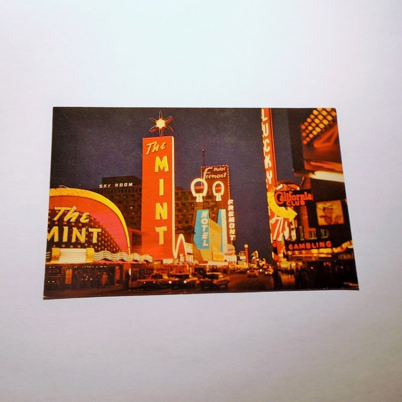 Vintage 1960s postcard of downtown Las Vegas Nevada. Features The Mint, Hotel Fremont, Lucky Casino, California Club, and others. Postally unused.