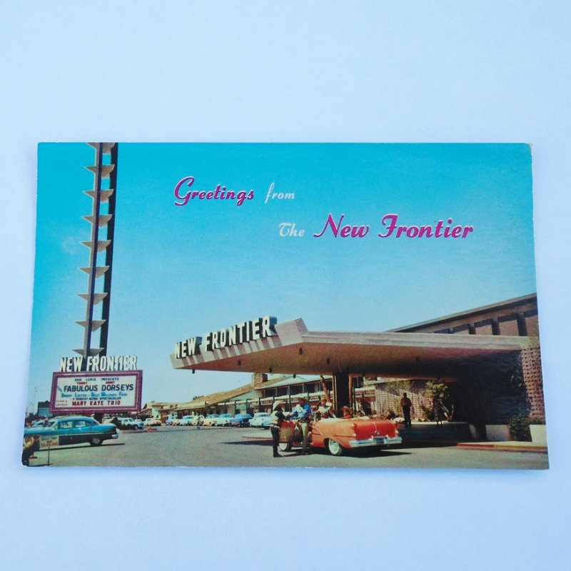 Vintage 1955 postcard of the New Frontier Hotel Casino in Las Vegas Nevada. The view is of the main entrance and marquee sign.