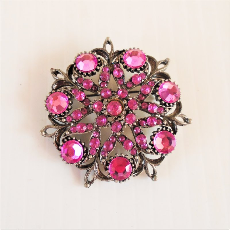 Floral design pin brooch. Measures 1.75 inches across. Sparkling cherry color. Wonderful condition. Estate find, unknown age.