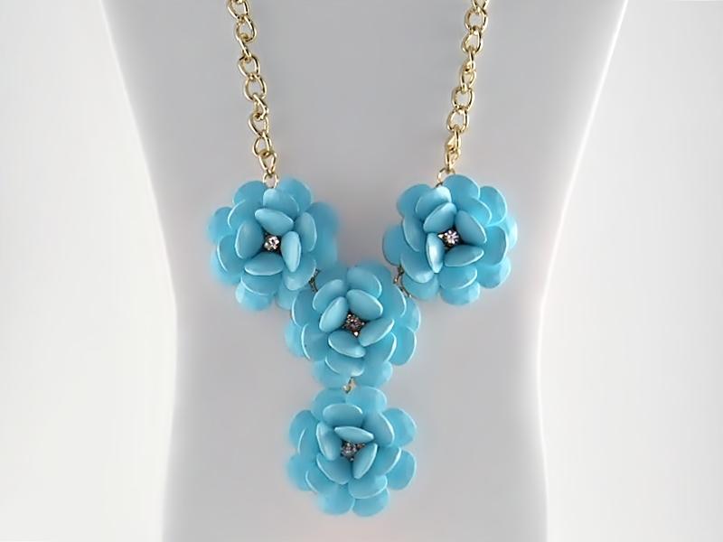 Light blue 4 flower rhinestone accented bib statement necklace on golden chain.