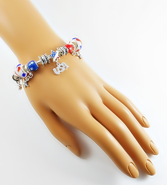 Silver snake chain charm bracelet with patriotic charm beads in red, white, blue and gold including dangle beads, large and small glass beads, and spacer beads.