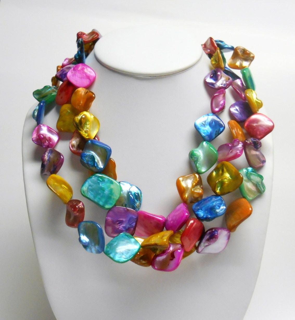 Three strands of vibrant rainbow multi color shells make up this unique necklace. The matching hook dangle earrings are made of the same pink and blue shells.