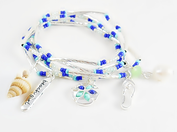 Set of 5 stretch bracelets with turquoise, blue and iridescent seed beads, silver tube beads and beach themed charms including a sand dollar, flip flop, sea shell, pearl bead, and beach girl.