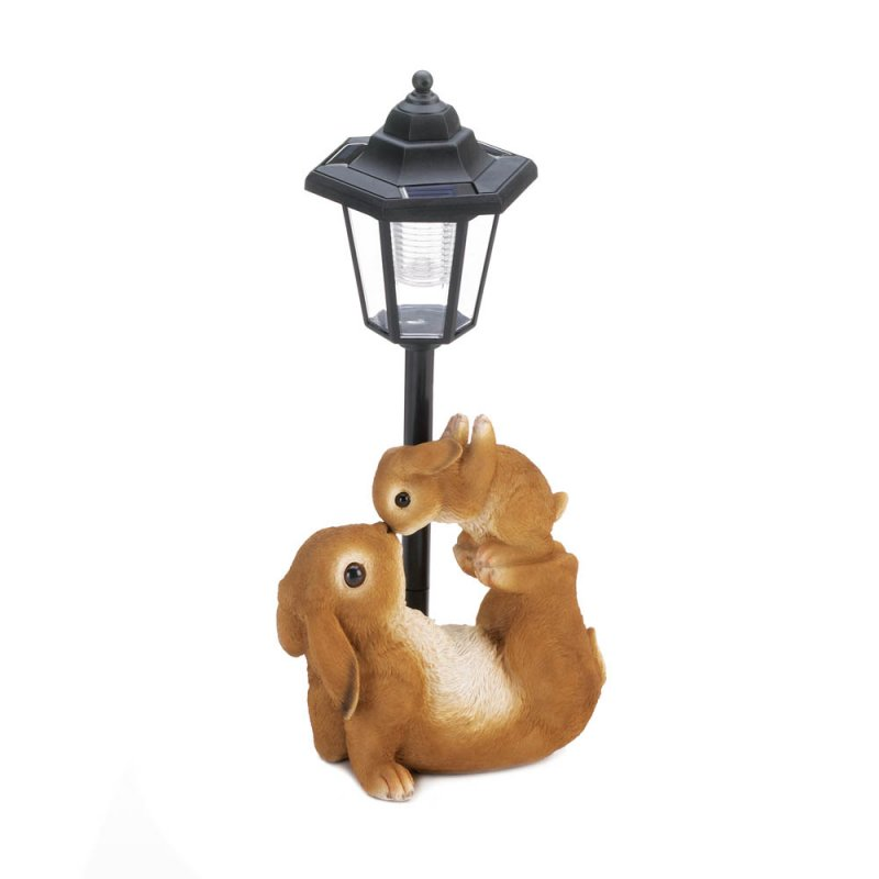 The garden light features a tree trunk base with two rabbit figurines.
