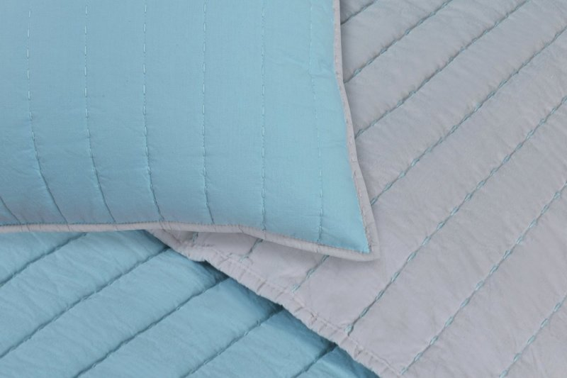 Quilt and pillow shams feature a luxurious horizontal triped stitching pattern.