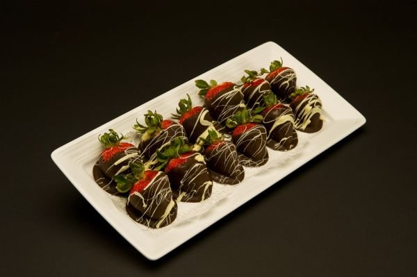 Six strawberries dipped in a dark chocolate couverture accented with a white chocolate drizzle.