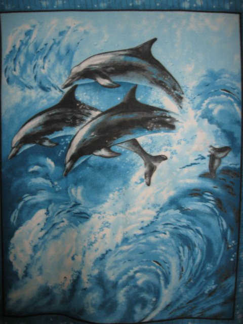 Dolphins in the ocean waves fleece blanket