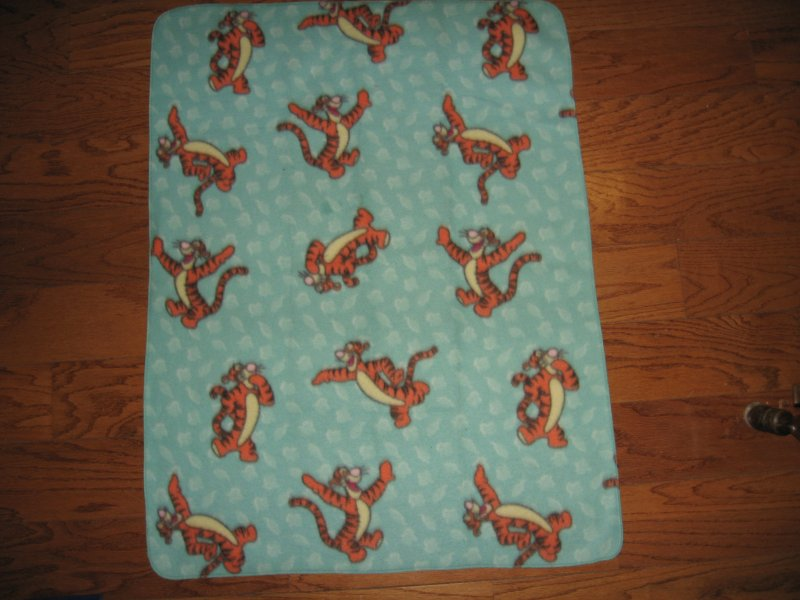 Image 1 of Tigger jumping around on a bluegreen soft  fleece baby blanket